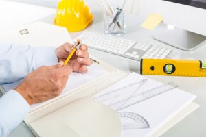 Close-up Of Architect Hands Sharpening a Yellow Pencil; Yellow Safety Helmet, Level and tools